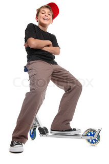 Low angle view of a relaxed boy sitting on the handlebars of a scooterHe has his feet apart, arms crossed and is smiling in a friendly manner