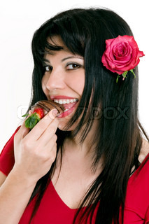 Beautiful female eating luscious strawberries, dipped in a coating of decadent chocolate