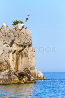 A man jumps off a cliff with a deep blue sea