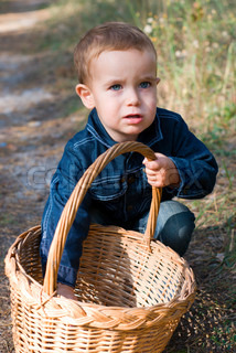 Cute boy with basket in a forest