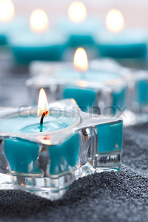 Close-up of blue candles in star shape holders on silver sand