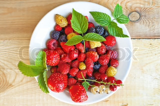 Strawberry, raspberry, blackberry, white and red currant, green leaves of strawberries and raspberry in white bowl on wooden boards