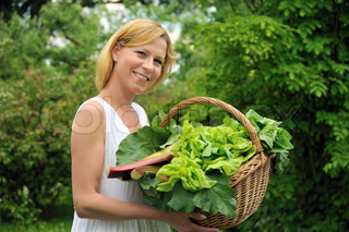 Young woman holding basket with vegetable