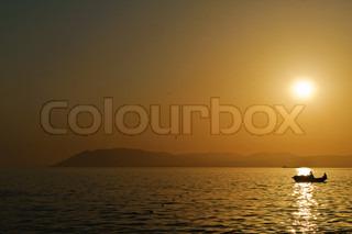 Ein kleines Schiff mit Menschen schwimmen im Meer unter den Sonnenuntergang