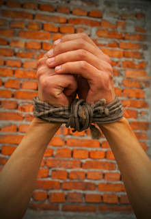 Hands tied up with rope against brick wall
