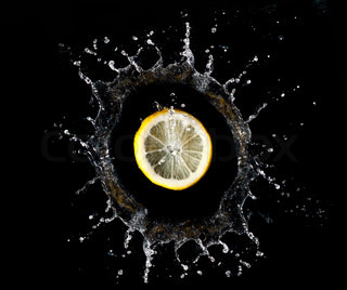 Lemon falling into water on black background
