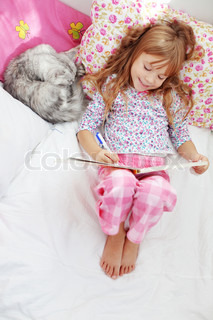 Portrait of child resting in bed with lovely pet