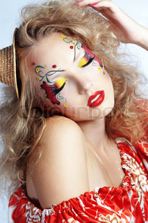 Stylish model with face paint and creative hairstyle