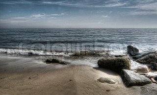 waves and rocks on a sandy beach hdr