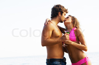 Young couple on the seaside with exotic cocktails is passionately kissing