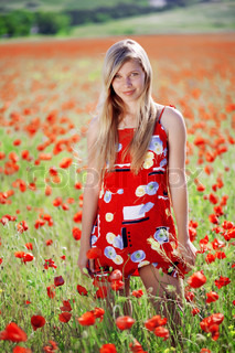 Blond girl in red dress posing at poppy meadow