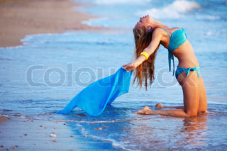Young beutiful sexy girl posing on beach in the water