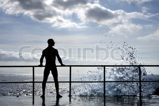 Silhouette of young man standing at the seaside, wave splash