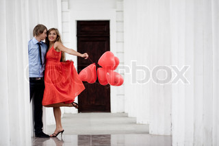 Young couple kissing among white columns and holding bunch of baloons-hearts