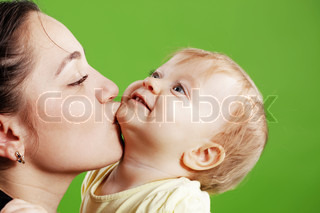 Mother kissing her baby over green close-up