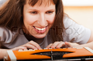 Smiling woman lying down floor typing text on old typewriter