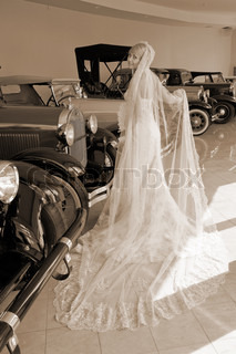 Retro styled picture with beautiful bride standing next old cars