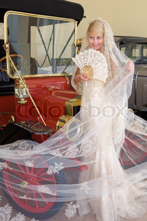 Beautiful bride with fan standing next antique car