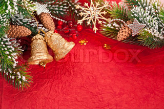 Christmas border from branch and decorations on red background