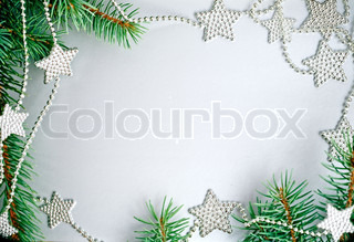 Christmas frame from branch and decorations on silver background