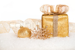 Gift box and gold decorations in snow on white background Christmas concept Shallow depth of field