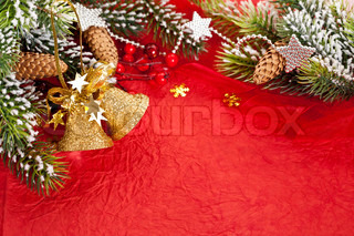 Christmas border from branch and decorations on red paper background