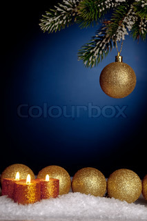 Gold Christmas tree decorations and candles in snow on blue background