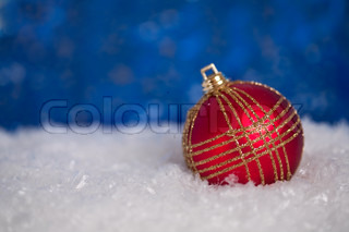 Red Christmas tree decorations in snow on blue background, shallow depth of field