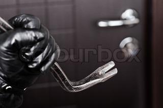 Gerningssted - kriminelle tyv eller indbrudstyv hånd i handske holder metal koben bryde åbning hjem dørlås