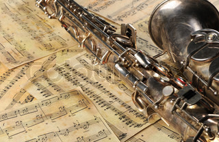 Old saxophone and notes The Musical instrument laying on notes with classical music of the beginning of 17 centuries