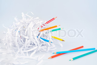 Colored pencils and shredded paper ball over light blue background with soft shadow - concept