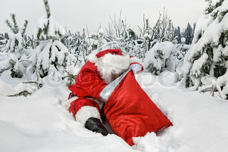 Santa Claus sitting looking for presents in his sack in the forest