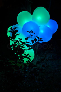 glowing green and blue inflatable balloons in tree branches
