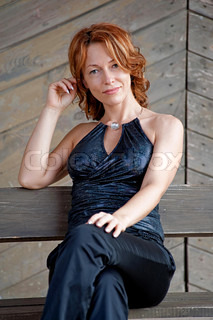 Beauty, mature woman sitting lean on old wooden board wall