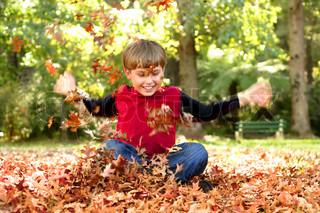 Kind beim Spielen in den Blättern und lachen gesellig