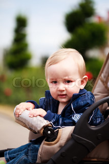 Sweet blonde toddler are sitting in baby carriage outdoor