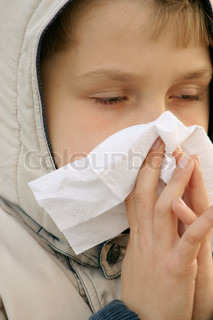Child blowing nose and looking unwell