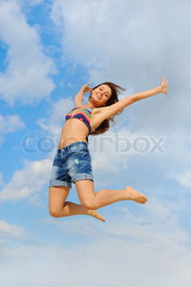 Beautiful young woman over blue sunny sky