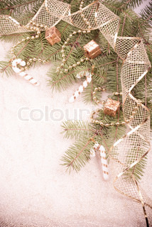 Gold Christmas ribbon, presents and beads on green pine branch