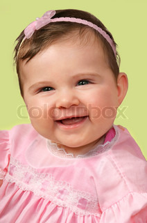 Beautiful happy baby girl wearing a pretty pink dress