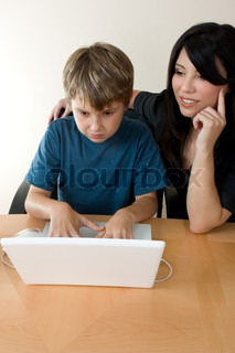 Child using a computer laptop with adult supervision or instruction