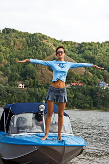 Happy young woman standing at the boat