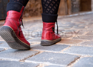 Woman walking on pavement - red boots