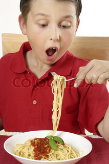 Hungry child boy eating spaghetti noodles and tomato based sauce
