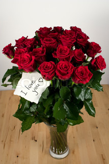 A bunch of roses in glass vase with note - I love you