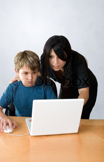 An adult assists a child using a laptop computer