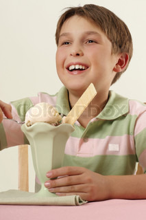 Smiling happy boy child sitting at a table with an ice cream sundae