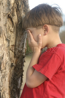 A child covering his eyes and counting - game of hide and seek