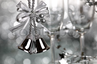 Christmas bells and two empty wineglass on silver background - shallow depth of field