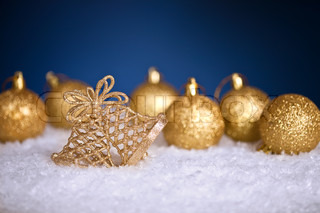 Gold Christmas tree decorations in snow on blue background